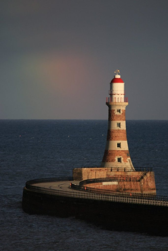 A_fading_rainbow_on_the_horizon_behind_Roker_Lighthouse_by_simon_c_woodley_simoncwoodley_1024x1024