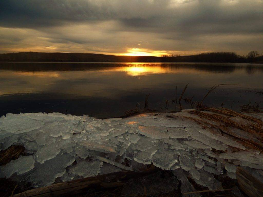 The last of the ice washes up on shore in Chicagoland at sunset
