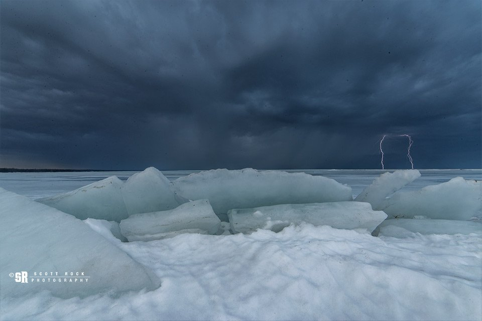 Double lightning bolts captured from the frozen shoreline of Saugeen Shores, Ontario by Scott Rock @scottrockphoto