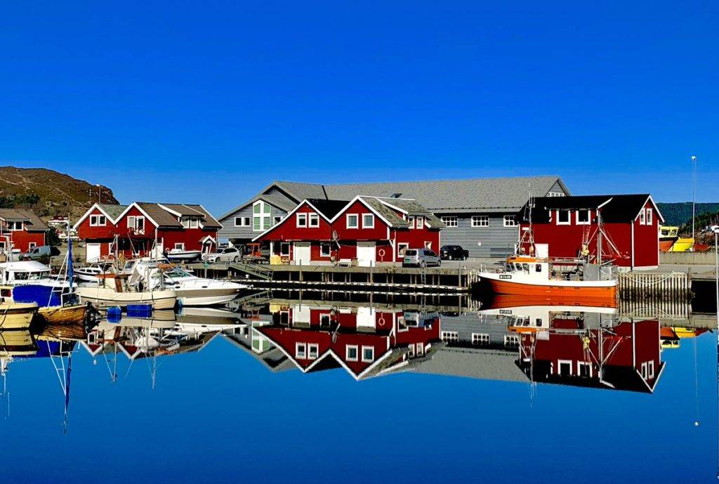 Crystal clear water with red boathouse in Norway by sirxxGray @bjornmgray