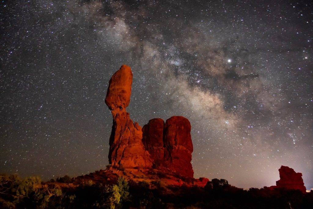 Milky Way galaxy rising over balanced rock in Arches National Park by Mike Kvackay @mkvackay