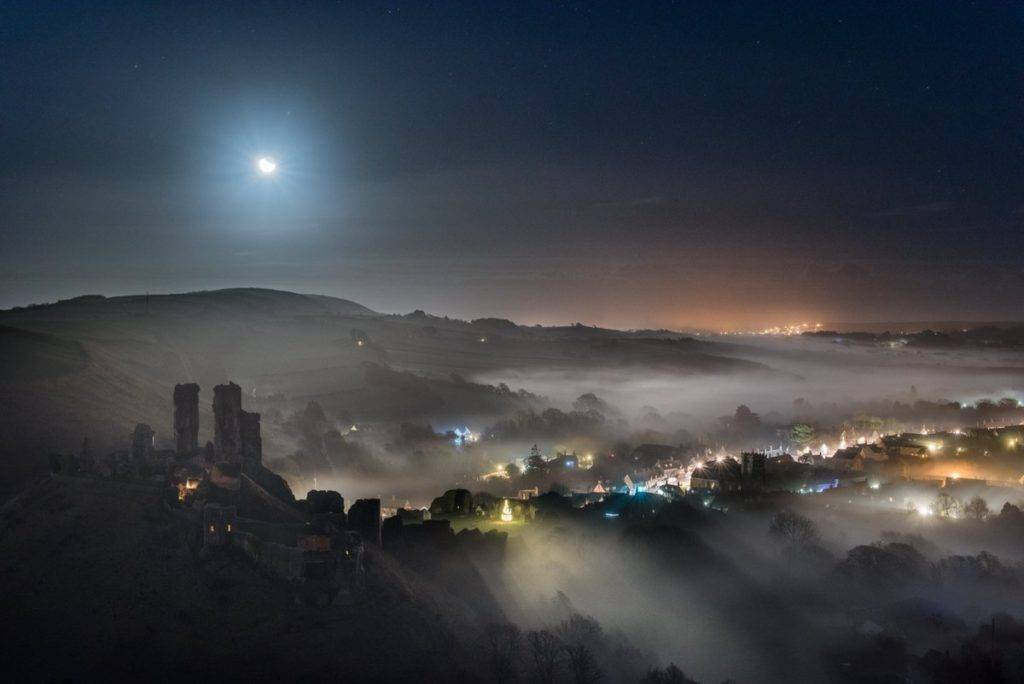 Moon over a misty Corfe Castle by Ollie Taylor @OllieTPhoto