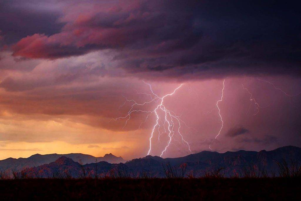 Lightning strikes in the mountains near Benson, AZ during a photogenic sunset monsoon storm by Mark J. Rebilas @rebilasphoto