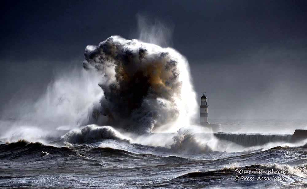 giant wave crashing over a lighthouse at Seaham in Durham UK