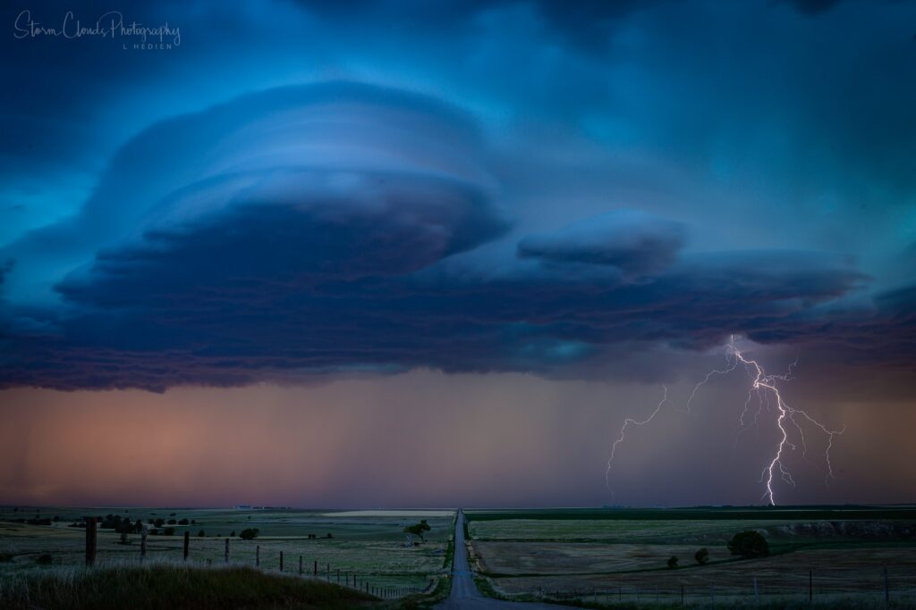 2nd Place Supercell and lightning bolts in a valley near Brewster Kansas by Laura Hedien @lhedien
